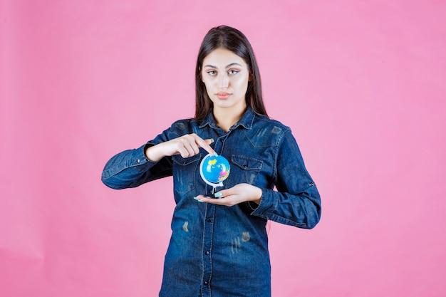 Ragazza in giacca di jeans che indovina posti sul globo