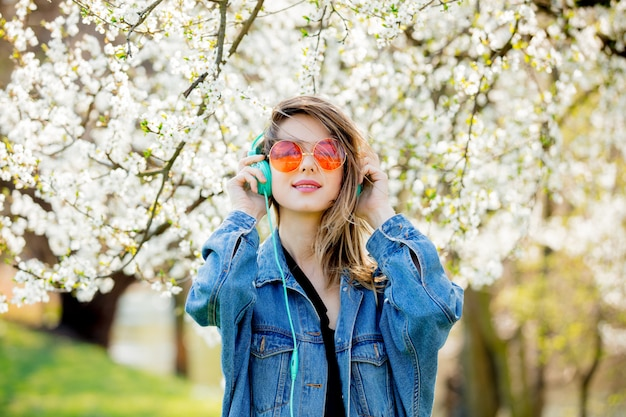 Girl in a denim jacket and headphones near a flowering tree