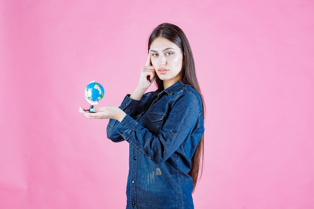 Girl in denim jacket holding a globe and thinking
