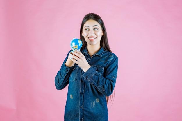 Girl in denim jacket holding a mini globe inside her palm