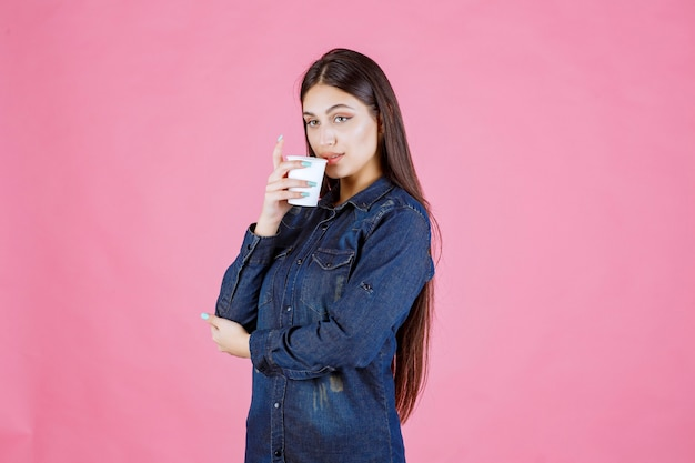 Girl in denim shirt drinking a cup of coffee