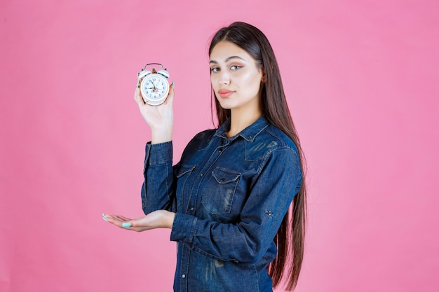 Girl in denim shirt holding an alarm clock and promoting it