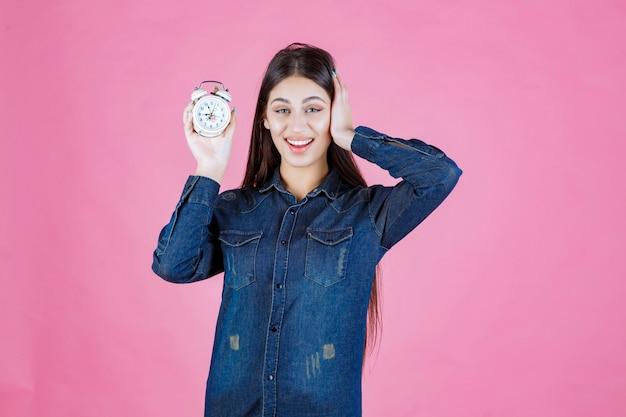 Ragazza in camicia di jeans che tiene una sveglia e la promuove