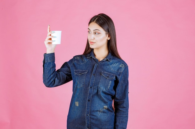 Girl in denim shirt holding a coffee cup and looks thoughtful and doubtful