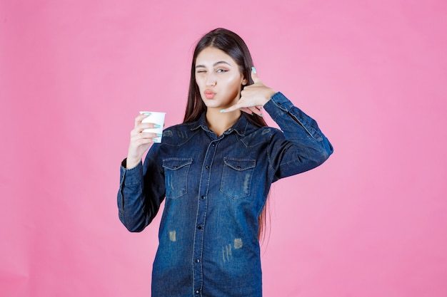 Girl in denim shirt holding a coffee cup and making call sign