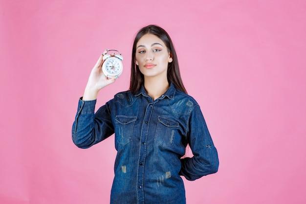 Ragazza in camicia di jeans che tiene e promuove una sveglia