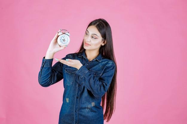 Ragazza in camicia di jeans che tiene e promuove una sveglia Foto Gratuite