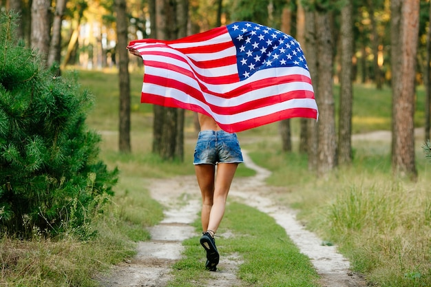 Girl in denim shorts running with american flag in hands.