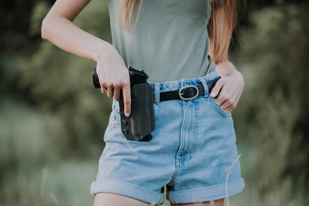 Girl in denim shorts and with a gun in his hand posing in the field. close up