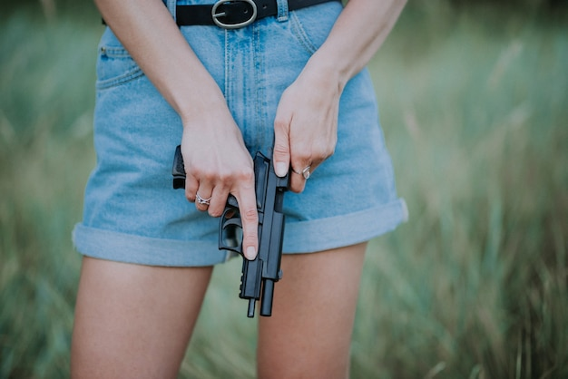 Girl in denim shorts and with a gun in his hand posing in the field.