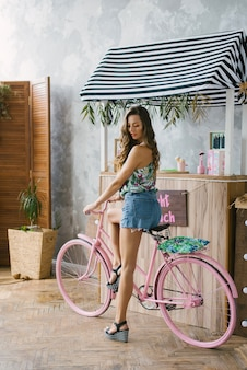Girl in denim shorts with long legs on a pink bike near the bar