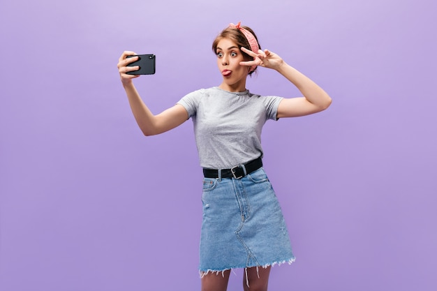 Girl in denim skirt demonstrates tongue, shows peace sign and takes selfie. funny woman in good mood in stylish clothes posing.