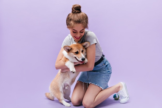Girl in denim skirt plays with corgi on purple background. cute young woman in trendy outfit holds corgi on isolated backdrop.