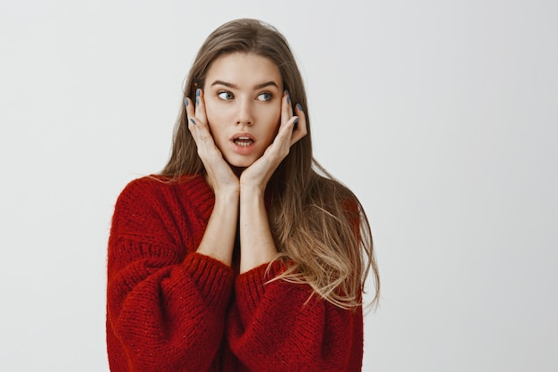 Girl did not know what to do after shocking revelation. indoor shot of worried attractive caucasian woman in stylish red sweater, holding palms on face and looking aside with troubled, confused face
