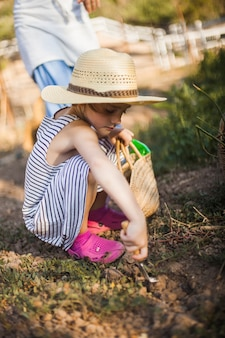 Girl digging the soil with trowel