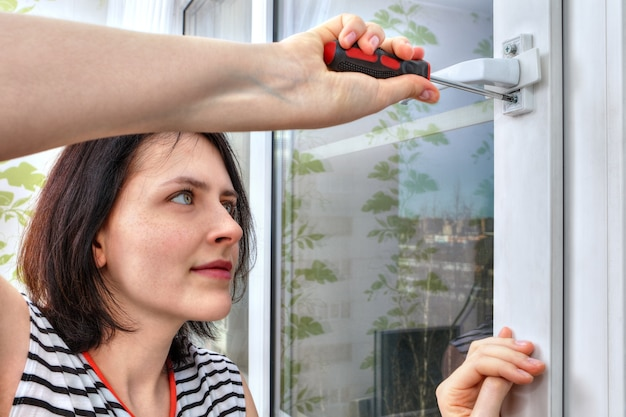 Girl dismantles window handle using screwdriver.