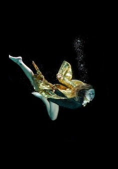 Girl diving with a golden cape