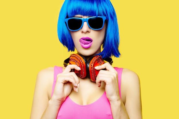 黄色の背景にヘッドフォンで音楽を聞いているかつらサングラスとピンクの水着の女の子dj。高品質の写真