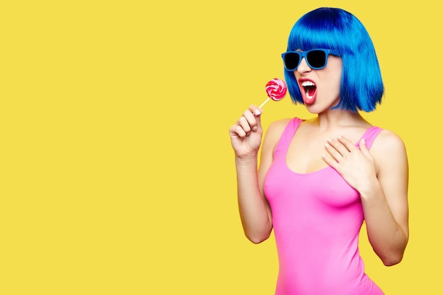 Girl dj in wig sunglasses and pink bathing suit listening music in headphones on yellow background. high quality photo