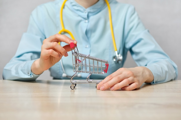 Girl doctor abstractly holds a shopping trolley.