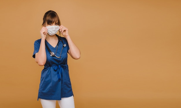 A girl doctor stands in a medical mask on a brown wall