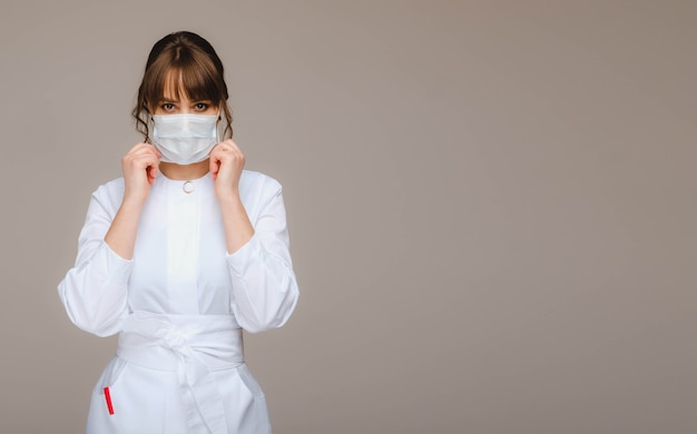 A girl doctor stands in a medical mask on a gray wall