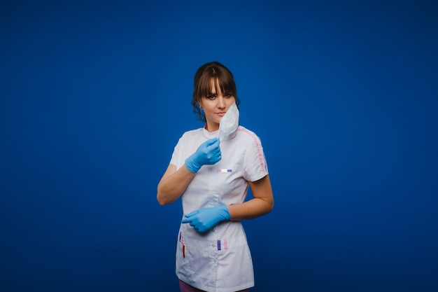 A girl doctor stands in a medical mask, isolated on a blue background.