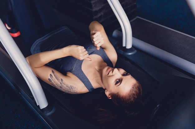 Girl does exercise the crunches while the treadmill