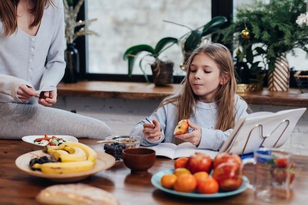 母親が料理をしている間、女の子は台所で宿題をします。
