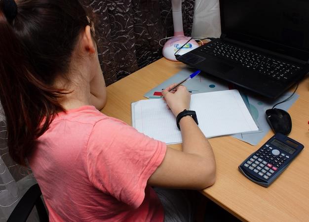 Девочка делает домашнее задание по математике. она сидит за столом, пишет ручкой в учебнике. онлайн обучение.