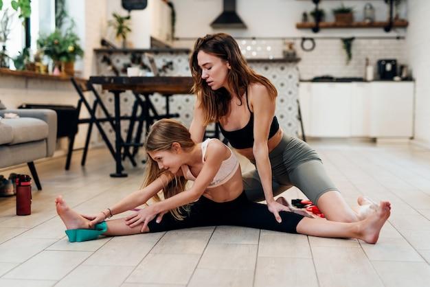 女の子はストレッチをし、母親は膝を抱えて彼女を助けます。