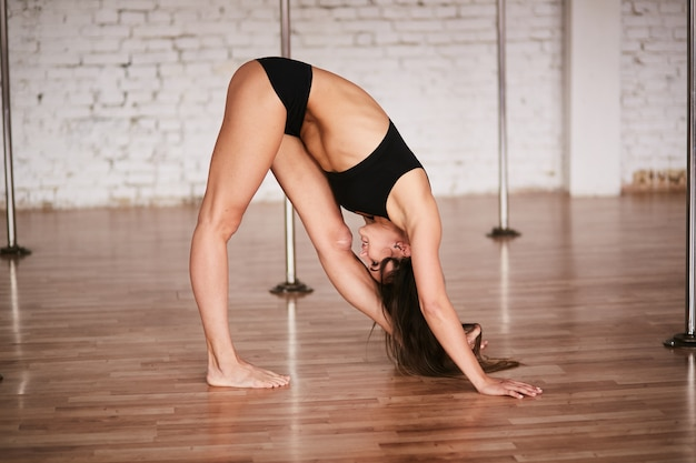 Girl does stretching of her back before a training in the pole dance gym