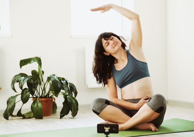 A girl does a workout at home - a girl sits on the floor and repeats exercises for a workout via video link