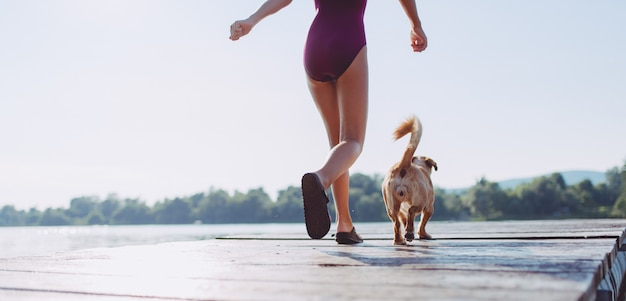 Girl and dog running together on the river dock