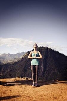 산 정상에서 균형을 잡고 서 있는 소녀