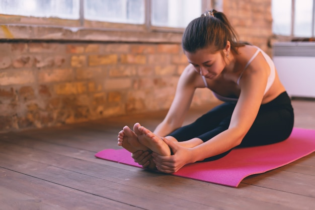 Girl doing an asana bending forward with her hands towards her legs