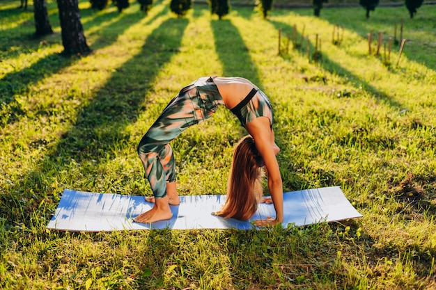 Girl doing asana with deflection back stands on hands on the lawn in the park