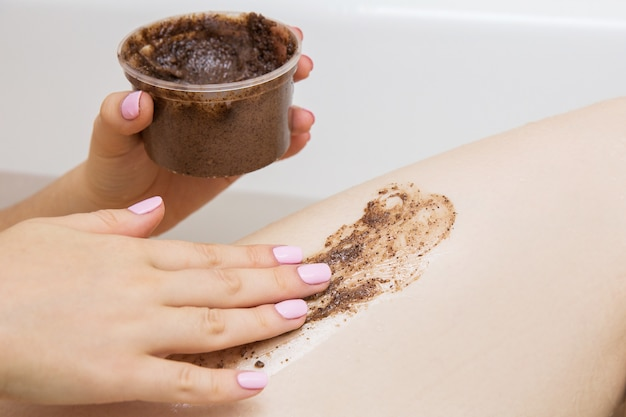 Girl doing beauty treatments in the bathroom. coffee scrub for foot