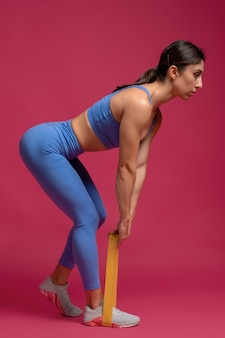 Девушка делает становую тягу с лентой сопротивления на темно-бордовой стене
