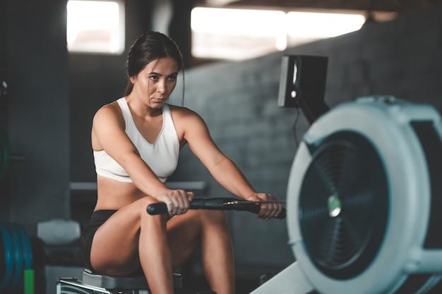 Девушка делает упражнения на гребном тренажере