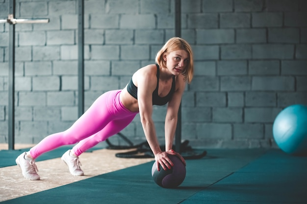 Girl doing exercise with a medical ball.