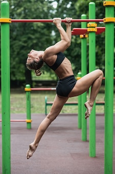 Girl doing exercises on the horizontal bar, the woman is engaged in workout