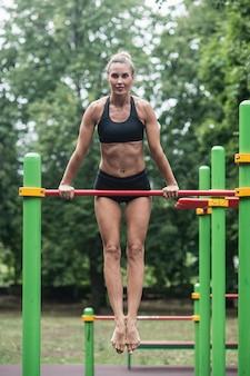 Girl doing exercises on the horizontal bar.