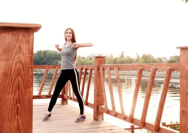 早朝のビーチで練習をしている女の子。スポーツ、健康的なライフスタイル、ボディケアの概念。