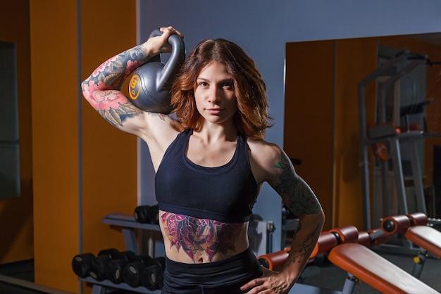 ダンベルで運動をしている女の子。フィットネスの入れ墨を持つ女の子は、筋肉のある美しい体を示しています。スポーツとフィットネスのためのさまざまなスポーツ機器とフィットネス機器