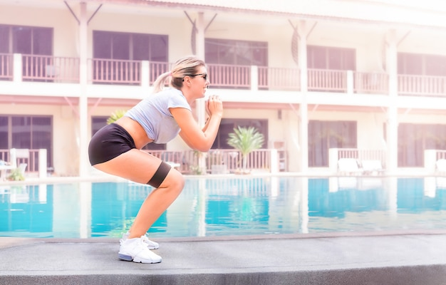 Girl doing exercises with resistance tape in the yard of the house