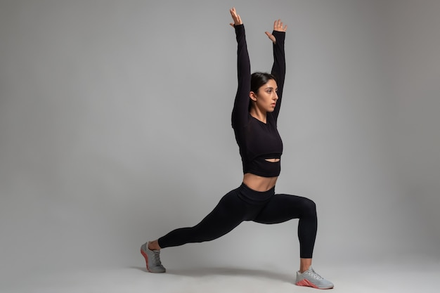 Girl doing forward lunges with arms stretched upwards on grey wall