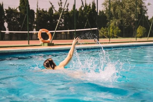 Ragazza facendo fronte strisciare nuotare in piscina