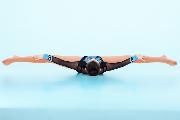 The girl doing gymnastics dance on a blue space