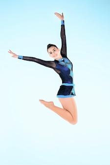 Girl doing gymnastics dance on blue